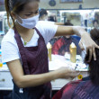 Thai hairdresser wearing a surgical mask - Stock Photo