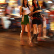 Two Thai woman walking through the city at night - Stock Photo