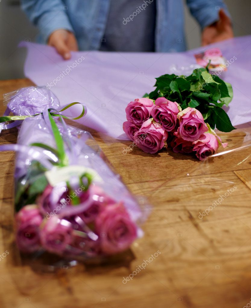 Cropped view of a florist preparing bunches of roses — Stock Photo #12240065
