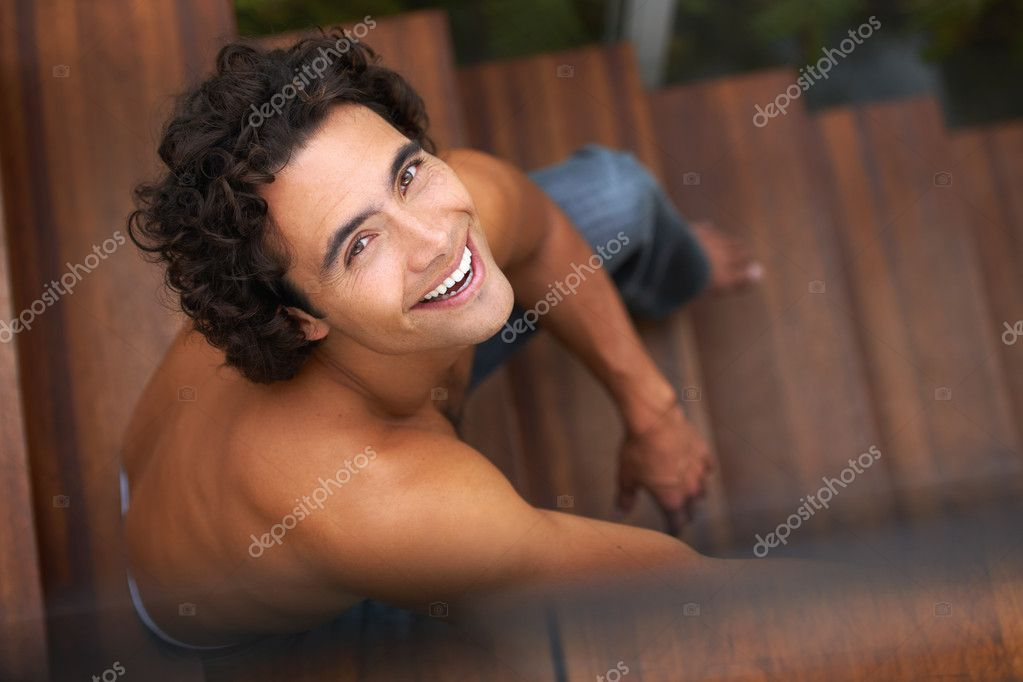 Gorgeous young man smiling up at you without a shirt on, sitting on a wooden stairway — Stock Photo #12240389