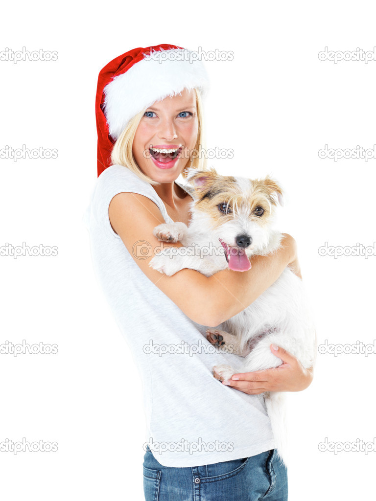 Cute young girl wearing a santa hat and looking excited while isolated on white and holding her jack russell terrier - portrait  Stock Photo #12241040