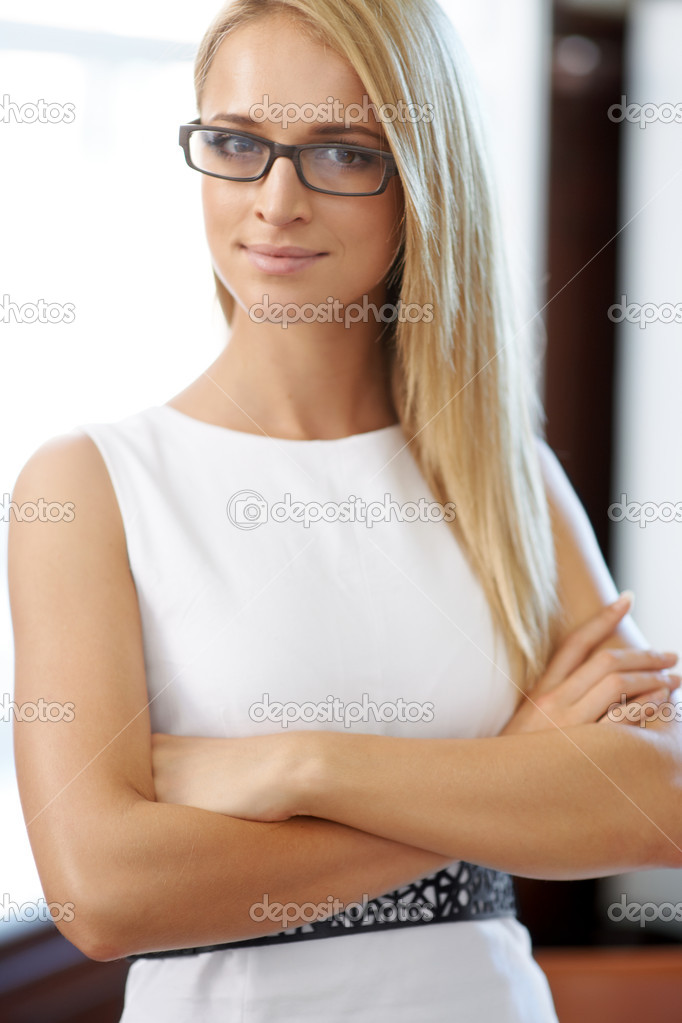 Portrait of attractive sophisticated blonde female looking stern with crossed arms  Stock Photo #12303555