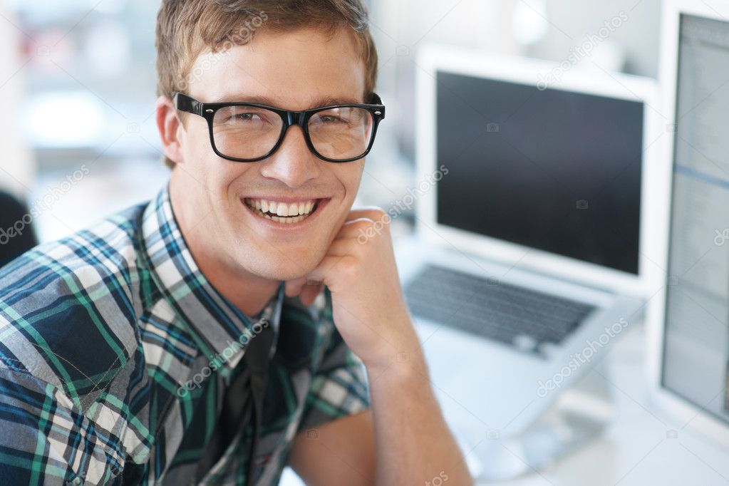 Portrait of smiling male geek employee with laptop in the background  Stock Photo #12303585