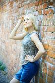 Sexy blonde lady standing near a brick wall — Stock Photo