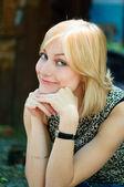 Cute blonde lady sitting near a wall — Stock Photo