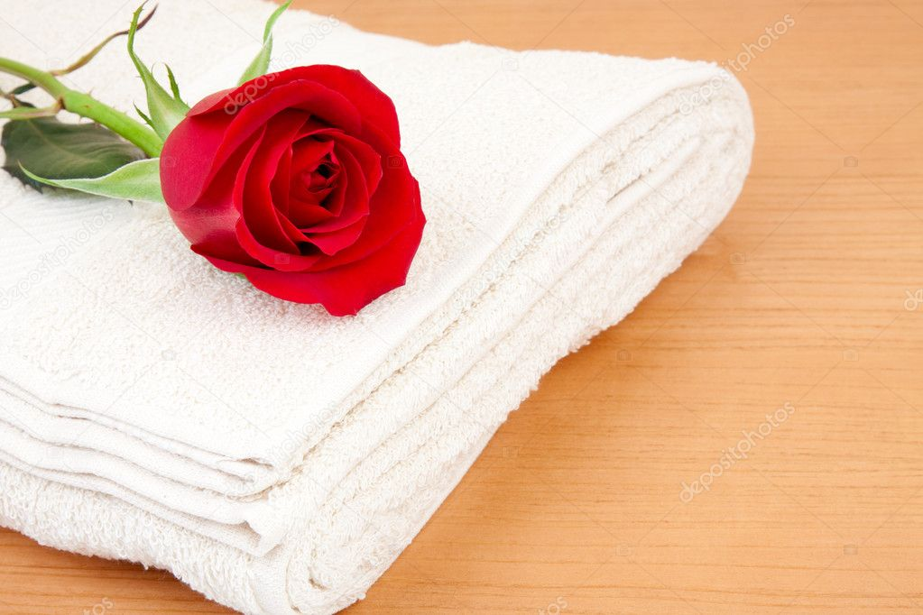 Red rose over a towel, placed in a wooden table. — Stock Photo #11921268