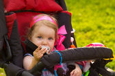 Little girl sitting in the stroller — Stock Photo
