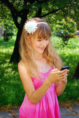 Young girl with mobile phone in park — Stock Photo