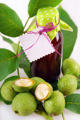 Fresh green walnuts and liqueur — Stock Photo