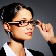 Young professional touching her glasses — Stock Photo