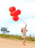 Glad tjej leker med sin ballonger — Stockfoto