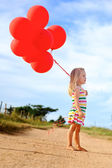 Cute young child with balloons — Stock Photo