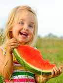 Cute blond girl happy with watermelon — Stock Photo