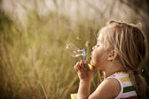 Happy girl blowing bubbles outdoors — Stock Photo