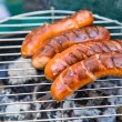 Tasty sausages burning on hot barbeque - Stock Photo