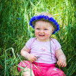 Cute infant baby girl sitting in grass — Stock Photo