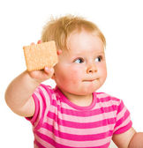 Infant baby learning to eat a biscuit — Stock Photo