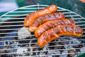 Tasty sausages burning on hot barbeque — Stock Photo