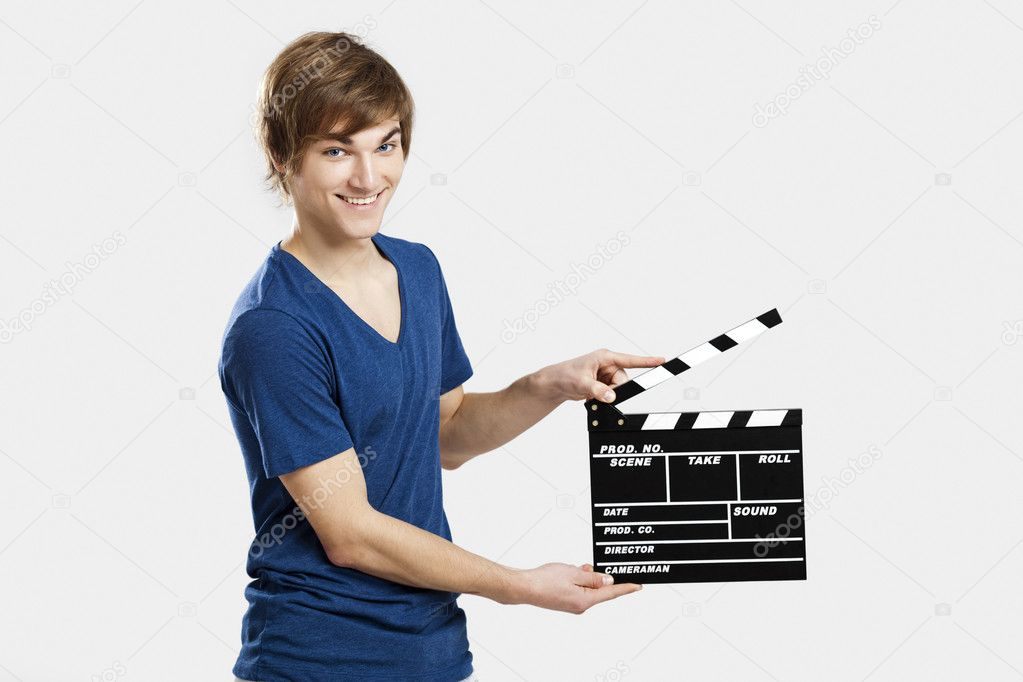 Casual young man holding a clapboard, over a gray background — Stock Photo #11787034