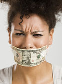 Covering mouth with a dollar banknote — Stock Photo