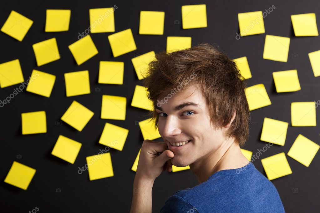 Young student in front of a board with yellow notes and looking in to the camera — Stock Photo #12317365