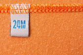 Label on orange cloth — Stock Photo