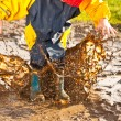 Child splashing in muddy puddle — Stock Photo