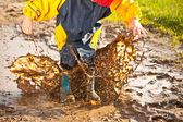 Child splashing in muddy puddle — Stock Photo