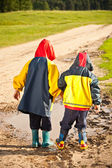 Brothers walking in puddles — Stock Photo