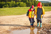 Two boys walking through a mud puddle — Stock Photo