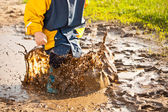 Child splashing in puddle — Stock Photo