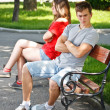 Foto Stock: Young couple sitting on bench in park