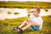 Chłopiec dmuchanie baniek w parku — Zdjęcie stockowe