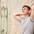 Young man leaning on a grunge wall — Stock Photo #11132505