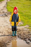 Boy in a muddy puddle — Stock Photo