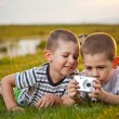 Brothers lying on meadow - Stock Photo