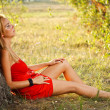 Woman sitting under tree in park — Stock Photo