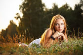 Young woman laying on a grass — Stock Photo