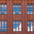 Brickwall facade with reflections of blue sky - Stock Photo