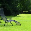 Chaise lounge on the green grass — Stock Photo