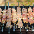 Many roast meat pieces on skewer. shish kebab cooking process — Stock Photo