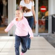 Little girl running in front mother — Stock Photo