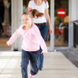 Little girl running in front mother — Stock Photo #10975914