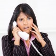 Businesswoman shocked by phone call — Stock Photo