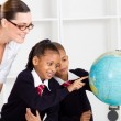 Stock Photo: Elementary geography teacher and students looking at globe