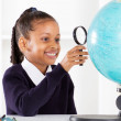 Primary schoolgirl looking at globe — Stock Photo