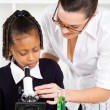 Friendly teacher helping primary schoolgirl — Stock Photo