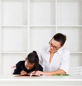 Caring tutor helping schoolgirl with homework — Stock Photo