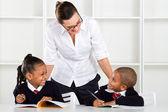 Elementary teacher talking to pupils — Stock Photo