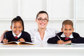 Caring primary teacher and students — Stock Photo